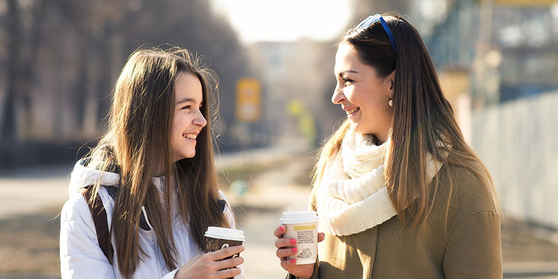 Mother and daughter talking outside over hot beverages