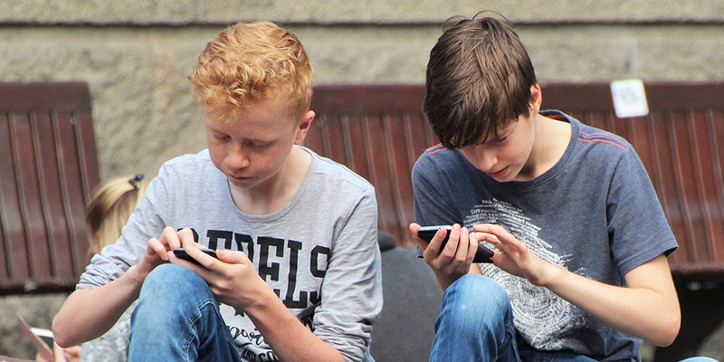 Two boys on their mobile devices